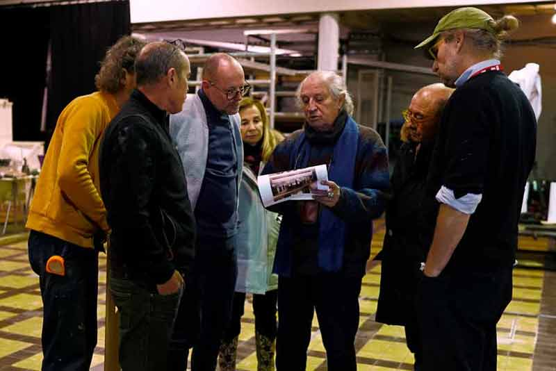 "Vittorio Storaro, a self-avowed perfectionist in his work, reviews some lighting details for the scene with Francesca Lo Schiavo, Dante Ferretti and a few members of ""The Living Tableau"" crew at the Academy One Studios. <span style=""""font-size: 9px;"""">© AFA vzw</span>"